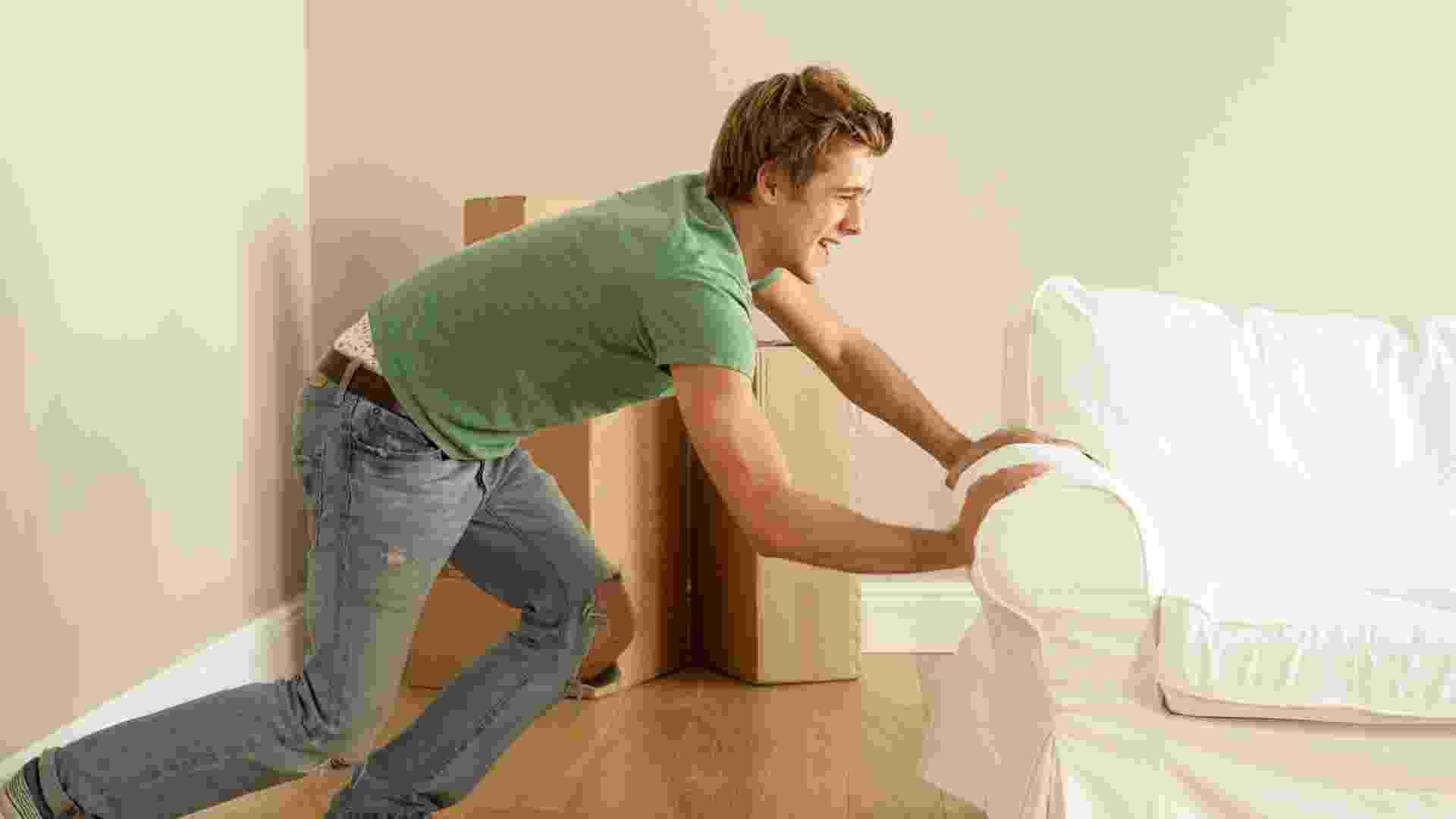 rapaz empurra sofá, limpeza em casa, mudança de casa, ilustra - Thinkstock