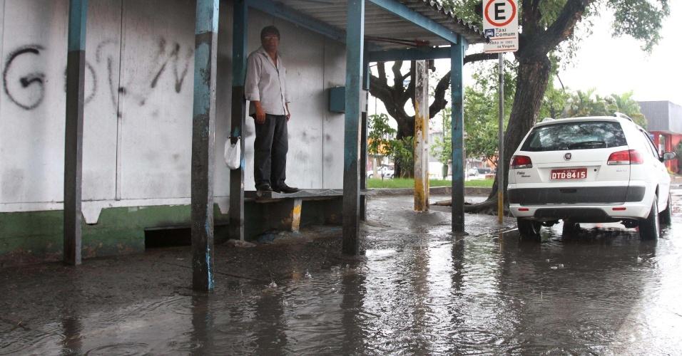 27.nov.2012 - Chuva alaga rua no largo do Limão, zona norte de São Paulo, e faz motorista de taxi subir em um banco para não se molhar