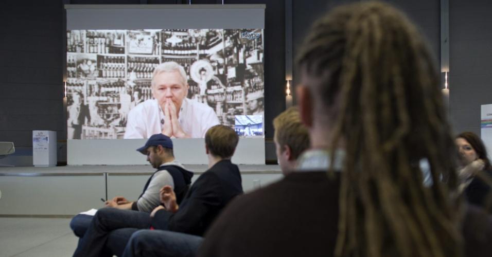 27.nov.2012 - Pessoas observam discurso de Julian Assange (no telão), fundador do site Wikileaks, transmitido ao vivo da embaixada do Equador em Londres, nesta terça-feira (27), em Hannover (Alemanha). Suspeito de cometer crimes sexuais na Suécia, Assange buscou refúgio na embaixada em junho. Segundo ele, as acusações tem motivação política