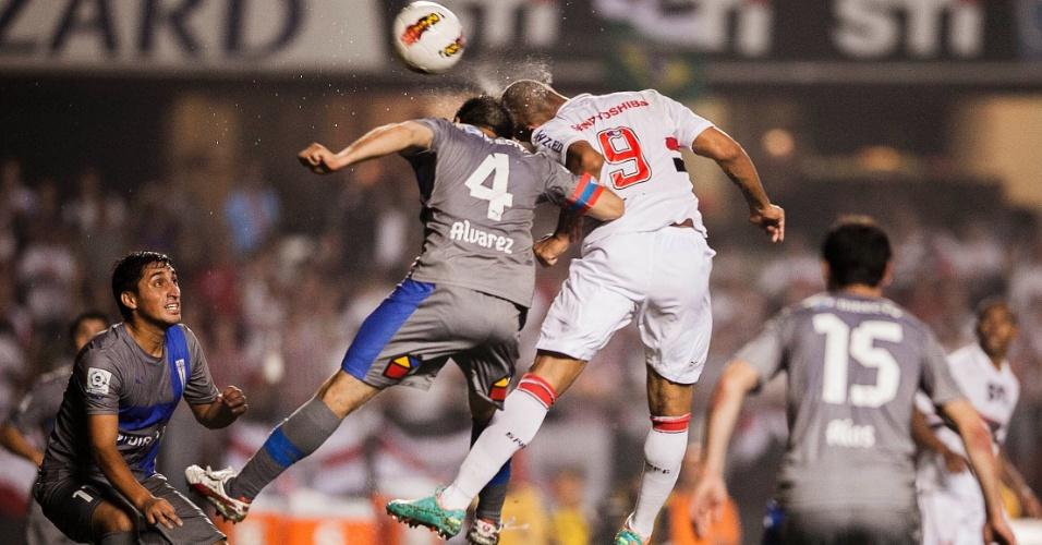 28.11.2012 - Luis Fabiano briga pela bola no alto com Alvarez, zagueiro da Universidad Católica