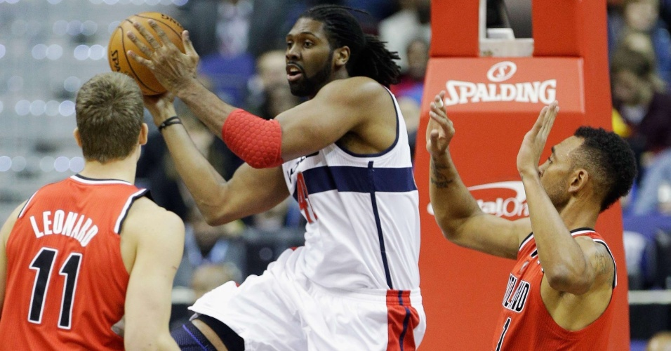 28.nov.2012 - Brasileiro Nenê, do Washington Wizards, tenta a jogada entre Meyers Leonard e Jared Jeffries, do Portland TrailBlazers