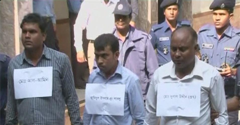 29.nov.2012 - Três supervisores de uma fábrica têxtil de Bangladesh são escoltados pela polícia após serem presos em Dhaka. Eles foram detidos durante manifestação em protesto contra incêndio supostamente criminoso que matou mais de 100 pessoas no último sábado (24)