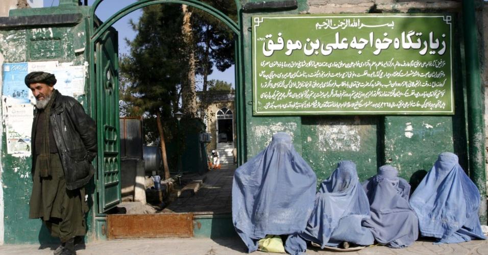 29.nov.2012 - Grupo de mulheres afegãs cobertas por burkas aguardam na entrada do templo Khawaja Ali bin Moofiq, nesta quinta-feira (29), em Herat de 2012