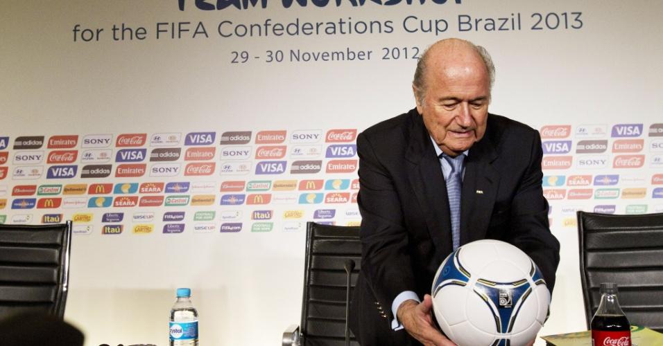 29.nov.2012 - Joseph Blatter, presidente da Fifa, arruma bola antes da coletiva da entidade sobre a Copa das Confederações, em São Paulo