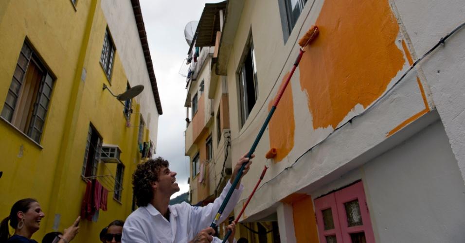 29.nov.2014 - O ex-tenista Gustavo Kuerten ajuda a pintar a fachada de uma casa no morro Santa Marta, no Rio de Janeiro. Nesta quinta-feira, o governo do Estado lançou um projeto, em parceria com uma fabricante de tintas, que tem a meta de pintar as fachadas dos cerca de 1,5 mil imóveis da comunidade até 2014