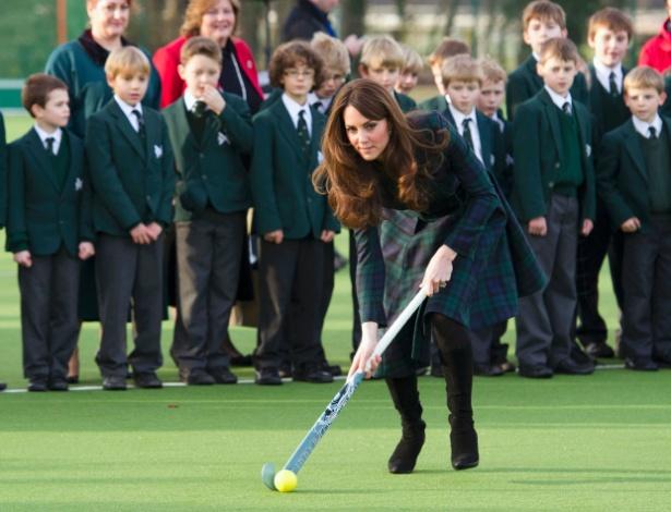 30.nov.2012 - A duquesa de Cambridge, Catherine Middleton, joga hoquéi durante visita à sua antiga escola, a St. Andrew's, em Berkshire, cidade ao sudeste da Inglaterra. Catherine é casada com o príncipe William, o segundo na linha de sucessão à coroa britânica