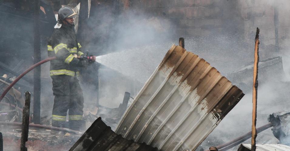 30.nov.2012 - Bombeiro controla as chamas de incêndio que atingiu a favela Paraisópolis, zona sul de São Paulo, nesta sexta-feira (30). Não há informações sobre possíveis feridos e as causas do incêndio