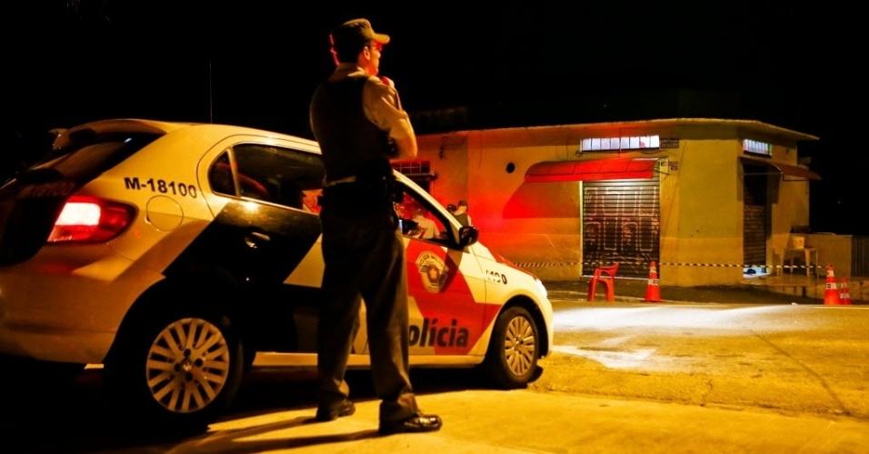 30.nov.2012 - Policial militar observa bar na esquina da estrada do Sabão com rua Lycurgo Antônio de Souza, na Freguesia do Ó, zona norte de São Paulo, onde quatro pessoas morreram e outras duas foram baleadas. De acordo com a polícia, dois homens em uma moto chegaram ao local e efetuaram vários disparos