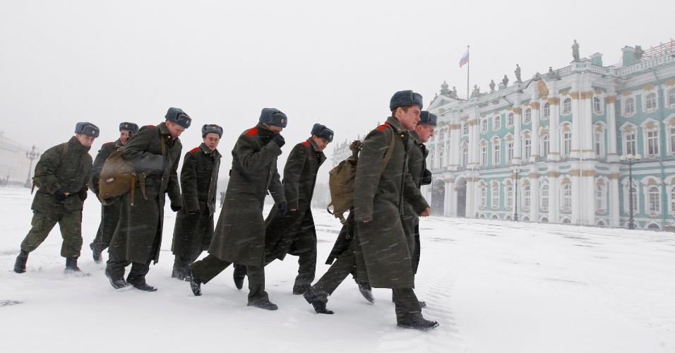 30.nov.2012 - Soldados russos caminham na neve em frente ao museu Hermitage, nesta sexta-feira (30), em São Petesburgo. Os termômetros registraram hoje temperaturas de 6º C negativos no local