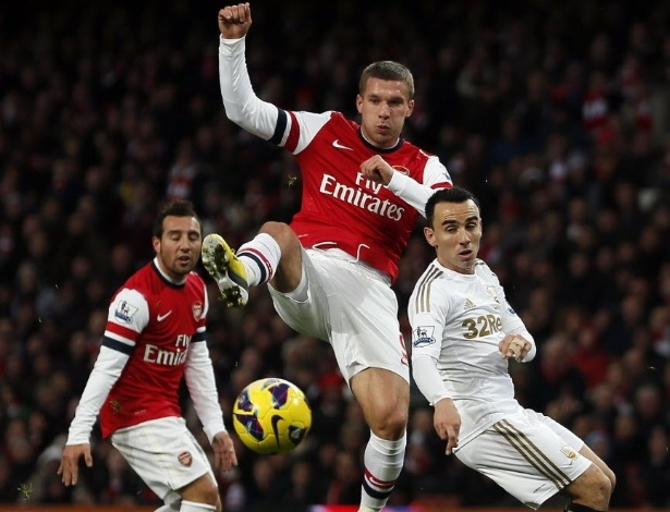 01.dez.2012 - Lukas Podolski (centro), atacante alemão do Arsenal, disputa a bola com Leo Brtton, do Swansea, em partida do Campeonato Inglês