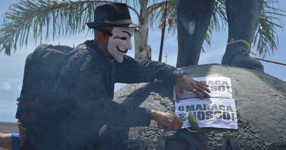 Manifestante cola papel com mensagem contrária à privatização do Maracanã em estátua próxima ao estádio