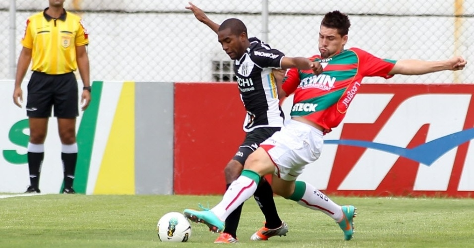 02.dez.2012 - Moises (dir), da Portuguesa, disputa a posse da bola na partida contra a Ponte Preta, no Canindé, pelo Campeonato Brasileiro