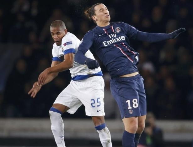 04.dez.2012 - Zlatan Ibrahimovic (dir.), atacante do PSG, disputa bola de cabeça com Fernando, do Porto, em partida da Liga dos Campeões, disputada em Paris