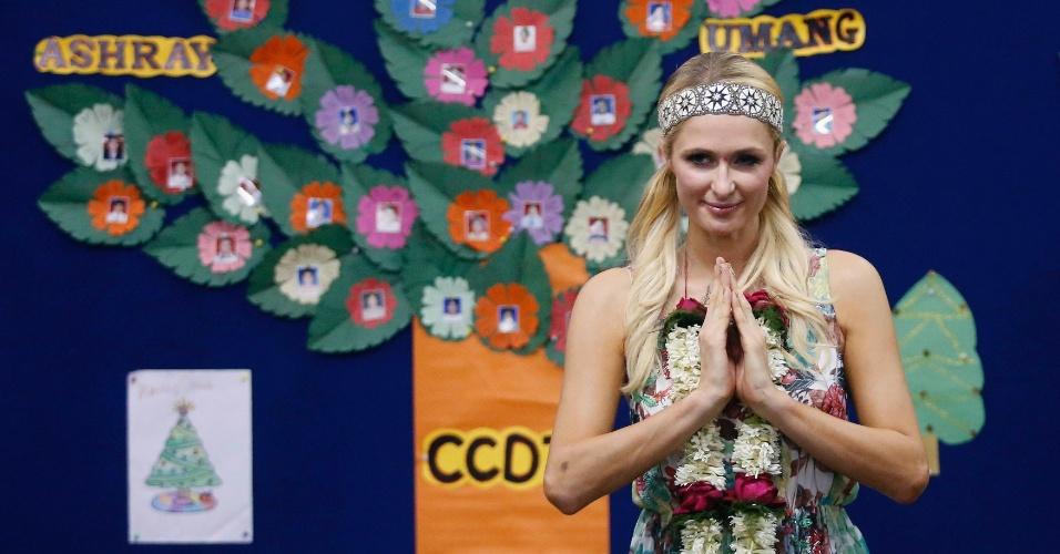 3.dez.2012 - Depois de participar do Fashion Week em Goa, a socialite Paris Hilton visitou um orfanato em Mumbai. A patricinha cantou com as crianças e vestiu roupas típicas do país