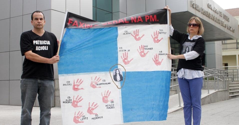 4.dez.2012 - Casal exibe faixa em protesto contra a PM, em frente a fórum em Niterói (RJ) onde é julgado o cabo Sérgio Costa Júnior, réu confesso no assassinato da juíza Patrícia Acioli, morta em agosto de 2011