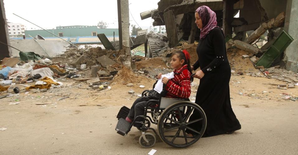 4.dez.2012 - Crianças palestinas com necessidades especiais passam em frente a prédio destruído durante conflito com tropas israelenses, em Gaza