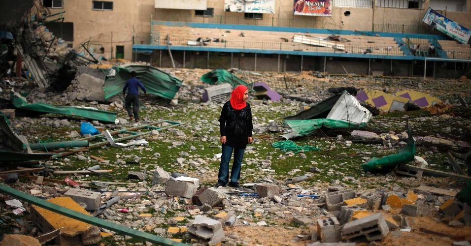 4.dez.2012 - Garota palestina caminha por estádio de futebol que ficou completamente destruído após ataque aéreo israelense, em Gaza
