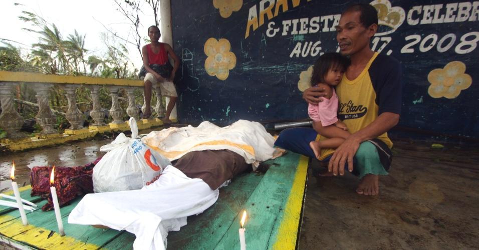 4.dez.2012 - Homem observa corpos de parentes mortos por deslizamentos provocados pelas fortes chuvas trazidas pelo tufão Bopha, que atingiu o sul das Filipinas