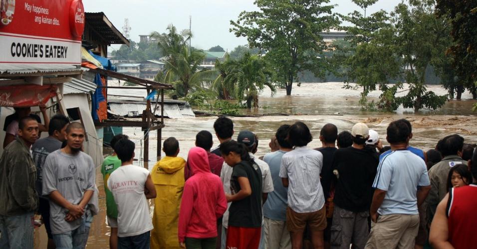 4.dez.2012 - Moradores observam nível da água do rio subir próximo a suas residências após a passagem do tufão Bopha  pelo sul das Filipinas