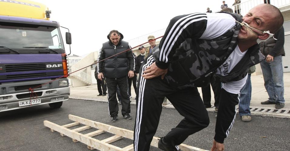 4.dez.2012 - O georgiano Lasha Patarava puxa um caminhão de 8,2 toneladas por uma corda presa em sua orelha na cidade de Rustavi, a 15 km de Tbilisi, na Geórgia, durante tentativa para bater recorde mundial e entrar para o Livro dos Recordes