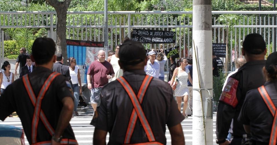 4.dez.2012 - Policiais observam protesto organizado por familiares da juíza Patrícia Acioli, nesta terça-feira, na porta do fórum de Niterói (RJ), durante intervalo do julgamento do cabo Sérgio Costa Júnior, réu confesso no assassinato da juíza