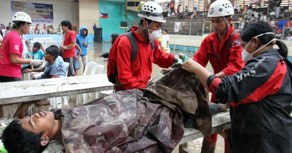 5.dez.2012 - Membros da Cruz Vermelha filipina prestam os primeiros socorros a sobrevivente de enchente causada pelo tufão Bopha, que atingiu o sul das Filipinas