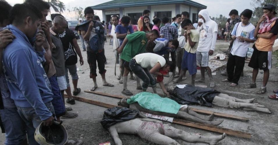 5.dez.2012 - Moradores procuram por parentes desaparecidos entre corpos de vítimas de enchentes causadas pela passagem do tufão Bopha pelo sul das Filipinas