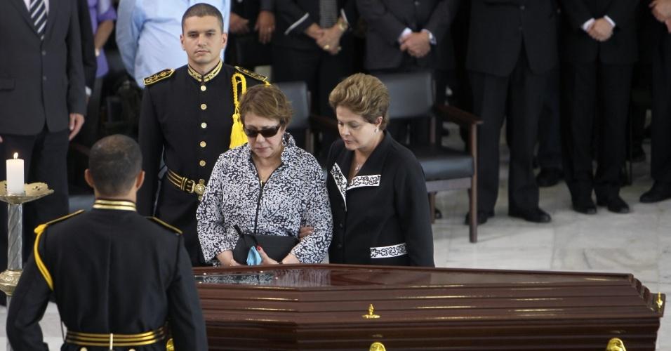 6.dez.2012 - A viúva de Oscar Niemeyer, Vera Lúcia Niemeyer, e a presidente Dilma Rousseff velam o corpo do arquiteto morto na noite desta quarta-feira (5), no salão do Palácio do Planalto, em Brasília. O arquiteto morreu na noite desta quarta-feira (5) em decorrência de problemas respiratórios, no hospital Samaritano, no Rio de Janeiro (RJ)