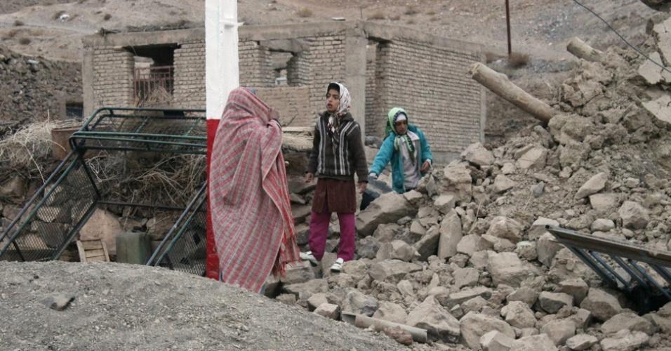 6.dez.2012 - Família caminha no meio dos escombros de prédio destruído após terremoto, em Shaj, no leste do Irã