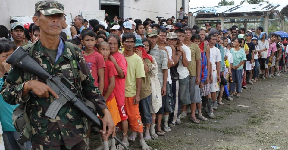 6.dez.2012 - Filipinos atingidos pelo tufão Bopha aguardam em fila para receber suprimentos na cidade de Nova Bataan, ao sul das Filipinas