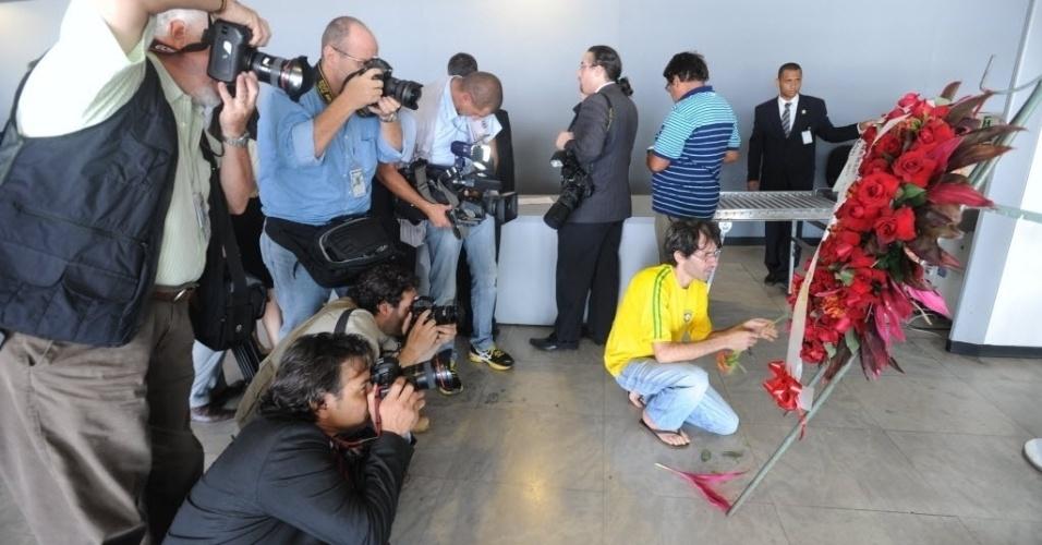 6.dez.2012 - Homem arruma coroa de flores enviada para o Palácio do Planalto, em Brasília, local do velório de Oscar Niemeyer