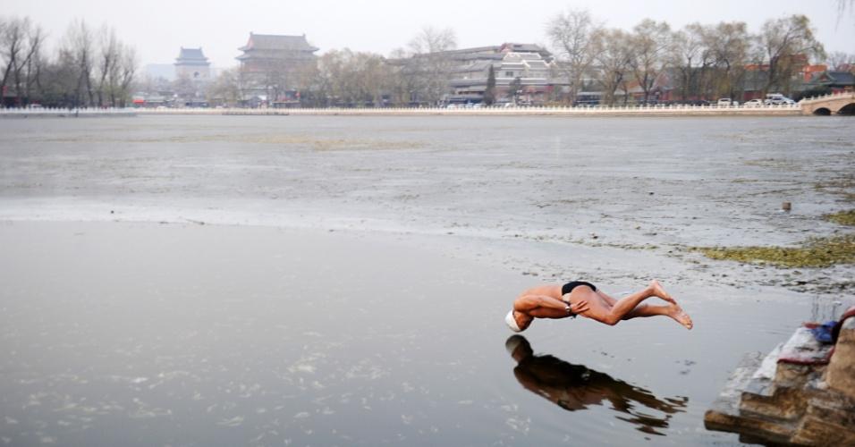 6.dez.2012 - Homem mergulha em lago parcialmente congelado, em Pequim, na China