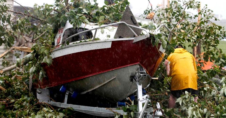 6.dez.2012 - Morador verifica um barco no meio do estrago causado pela passagem de um tornado na periferia de Auckland, Nova Zelândia, nesta quinta-feira (6). Três pessoas morreram e diversas ficaram feridas em decorrência do que testemunhas descreveram como um minitornado, que varreu a maior cidade do país
