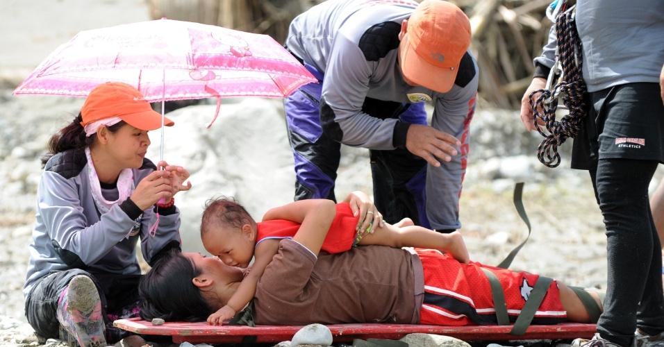 6.dez.2012 - Mulher abraça seu filho enquanto se prepara para ser transportada sobre um rio em cidade do sul das Filipinas