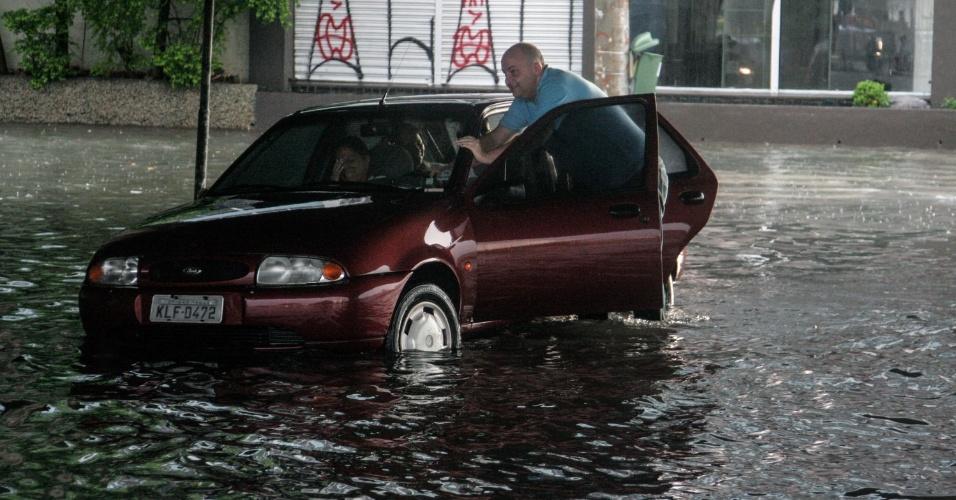 Homem empurra carro na Radial Leste, em São Paulo (SP), nesta quinta-feira (6), que alagou por causa da forte chuva que atingiu a capital nesta quinta-feira