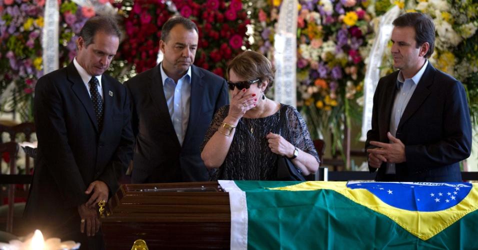 7.dez.2012 - A viúva de Oscar Niemeyer, Vera Lúcia, observa caixão com o corpo do arquiteto acompanhada pelo governador do Rio, Sérgio Cabral (centro), e pelo prefeito do Rio, Eduardo Paes (dir.)
