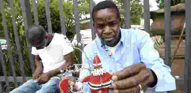 Artesão sul-africano trabalha na confecção de enfeites de Natal, nesta sexta-feira (7), em Johannesburgo - Stephane De Sakutin/AFP - Stephane De Sakutin/AFP