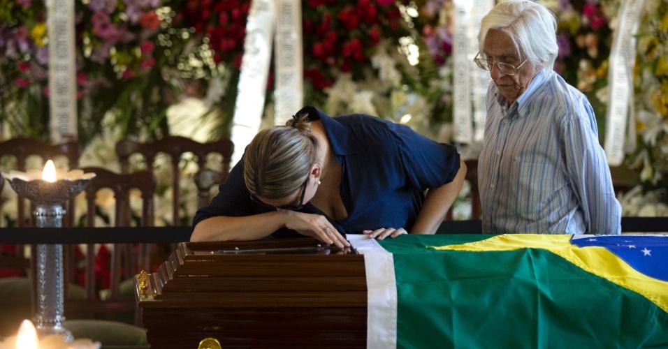 7.dez.2012 - Ao lado do poeta Ferreira Gullar, mulher chora diante de caixão com o corpo de Oscar Niemeyer durante velório que acontece no Palácio da Cidade, sede oficial da Prefeitura do Rio de Janeiro