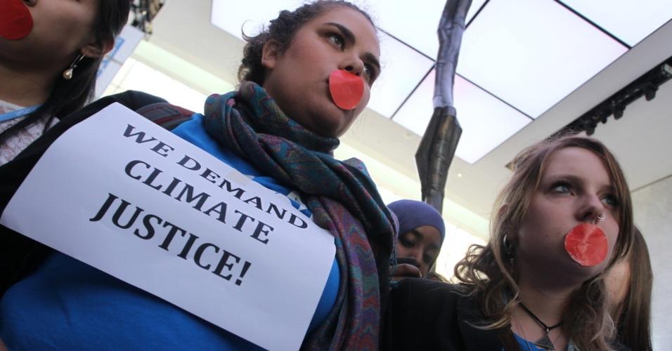 7.dez.2012 - Mulheres protestam no último dia da COP 18, cúpula anual da ONU (Organização das Nações Unidas) sobre o clima - o cartaz traz a frase 'nós exigimos justiça para o clima'. Ativistas de ONGs pedem que os países ricos firmem compromissos e apoios financeiros para ações de mitigação e adaptação para as mudanças climáticas