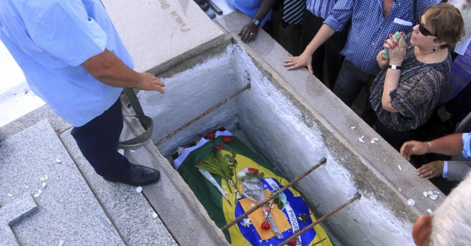 7.dez.2012 - Vera Lúcia Niemeyer (dir.), mulher do arquiteto Oscar Niemeyer, se despede do marido durante seu enterro nesta sexta-feira, no cemitério São João Batista, na zona sul do Rio de Janeiro. Caixão foi enterrado com a bandeira brasileira e rosas vermelhas