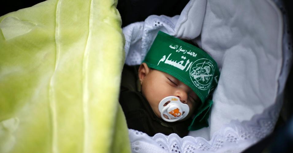8.dez.2012 - Bebê palestino usando uma bandana do Hamas dorme durante a celebração do 25º aniversário do grupo que controla a Palestina. A festa acontece na praça Katiba, na faixa de Gaza