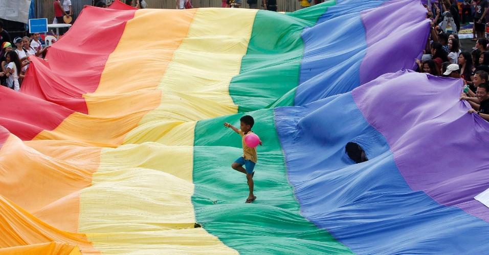 8.dez.2012 -Menino dança em cima da bandeira do orgulho gay em Makati, no sul de Manila, nas Filipinas. Mesmo com os estragos provocados pela passagem do tufão Bopha, que deixou mais de 500 mortos e centenas de desabrigados, a comunidade LGBT manteve a parada