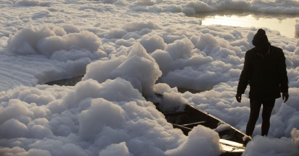 9.dez.2012 - Indiano observa barco coberto de espuma poluída no rio Yamuna, em Nova Déli
