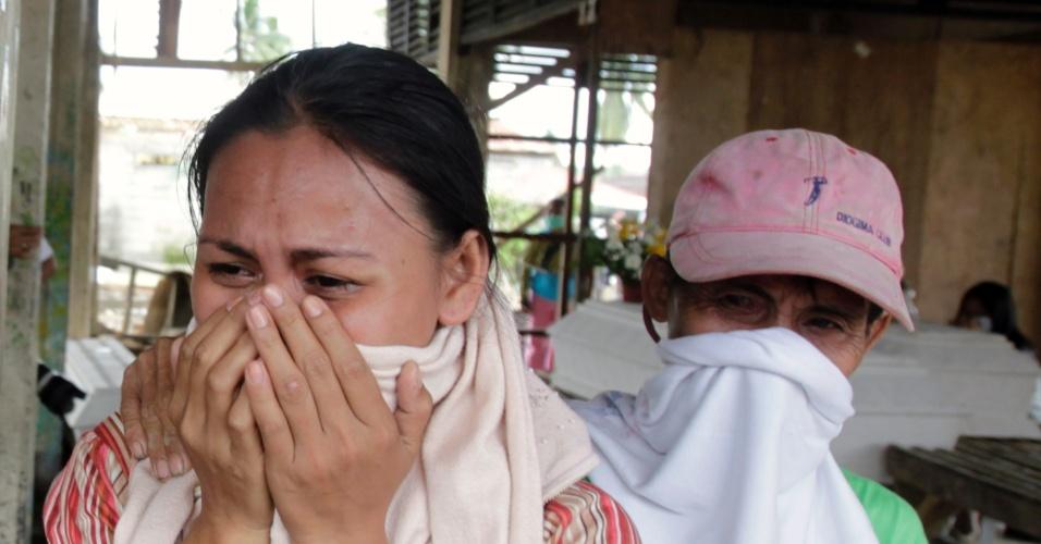 9.dez.2012 - Mulher chora ao avistar caixões com corpos de parentes vítimas do tufão Bopha em necrotério em New Bataan (Filipinas)