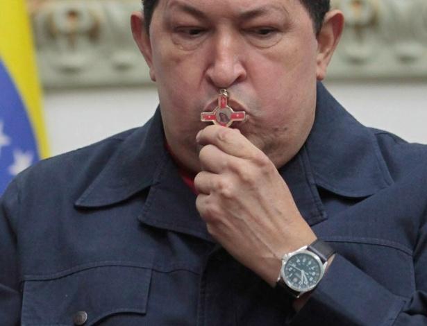 9.dez.2012 - O presidente venezuelano, Hugo Chávez, beija crucifixo durante pronunciamento nacional no Palácio de Miraflores, em Caracas