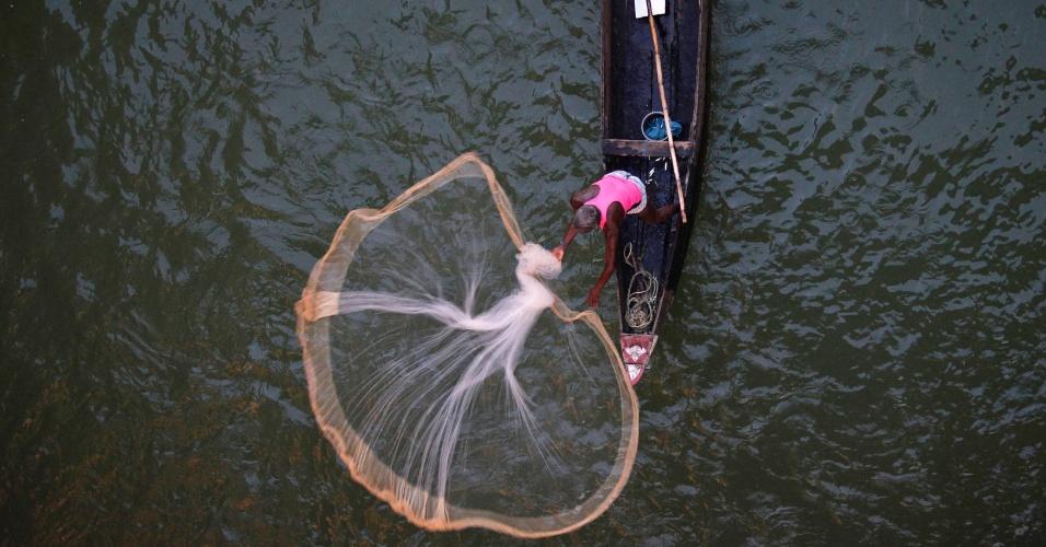 9.dez.2012- Pescador joga rede no rio Kathajodi, nas redondezas da cidade de Bhubaneswar, na Índia