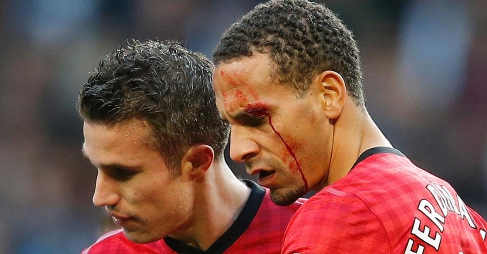 09.dez.2012 - Ao lado de Van Persie, Ferdinand, zagueiro do Manchester United, exibe o corte no supercílio esquerdo após ser atingido por uma moeda na vitória por 3 a 2 de sua equipe contra o Manchester City