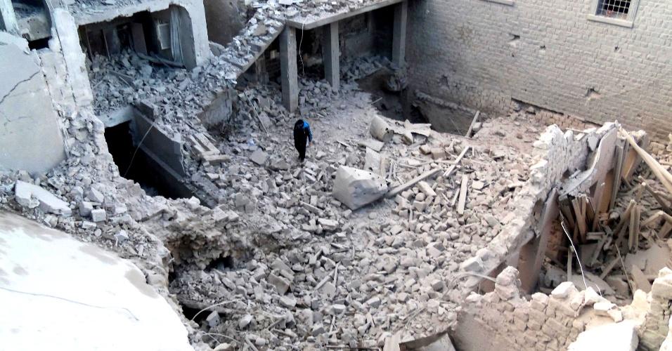 10.dez.2012 - Homem caminha em meio a ruínas de prédios em Homs, na Síria. De acordo com ativistas, os prédios foram destruídos por mísseis lançados pela força áerea do regime do ditador sírio Bashar Assad