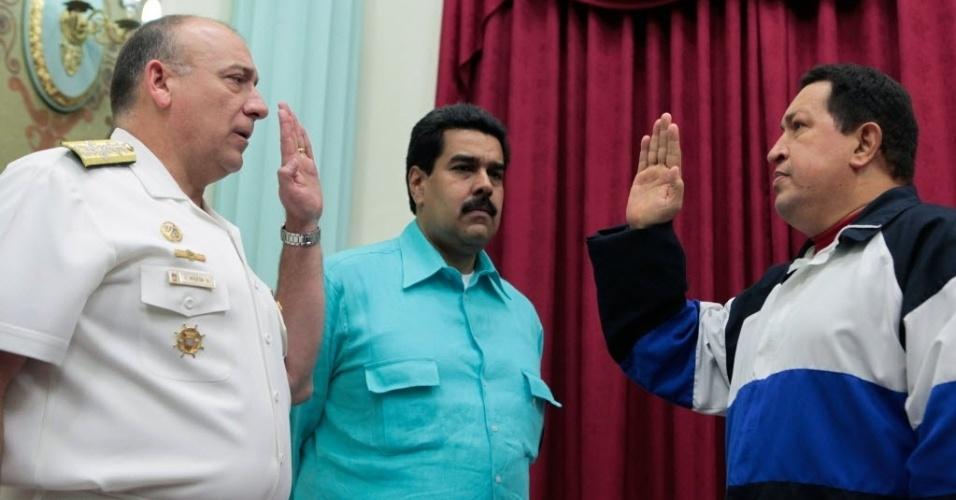 10.dez.2012 - O presidente da Venezuela, Hugo Chávez (dir.), juntamente com o vice-presidente, Nicolas Maduro (centro), realiza o juramento do novo ministro da Defesa, Diego Molero, em Caracas, capital do país