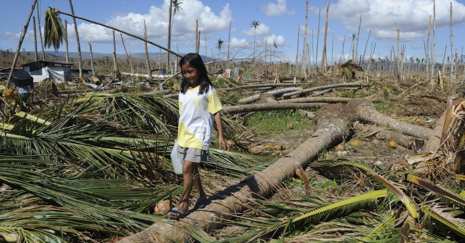 10.dez.2012 - Garotinha caminha para buscar água em Baganga, dias após a passagem do tufão Bopha